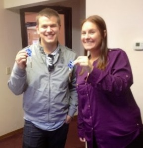 New resident and leasing agent displaying keys to apartment