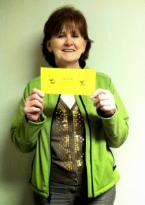 Resident Jackie holding a certificate for the early bird contest winner