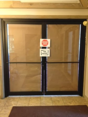 Photo of party room doors covered in paper and showing two signs.