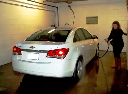Photo of woman washing car in car wash bay.