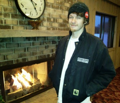 Photo of James dressed in his jacket and standing next to a fireplace.