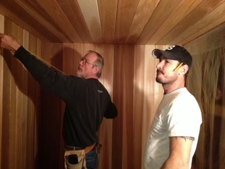 Robert and Ryan measuring materials they'll need for the sauna.